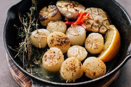 Гребешки с чесночным маслом и травами на сковороде