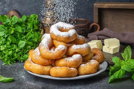 Большая порция пончиков с сахарной пудрой