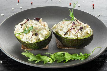 Две половинки авокадо, фаршированные крабовым салатом