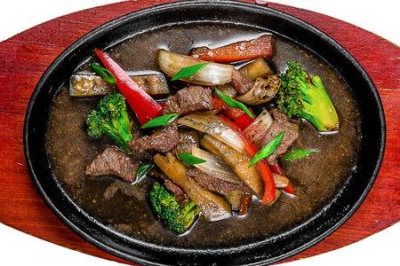 Говядина с овощами на шипящей сковороде