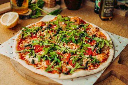 Пицца с моцареллой, помидорами, листьями рукколы