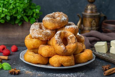 Большая порция пончиков с сахарной пудрой и корицей