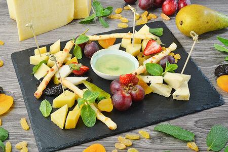 Ассорти сыров на камне с фруктами и медом