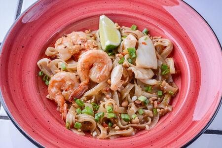 Рисовая лапша с овощами и морепродуктами, обжаренная на воке