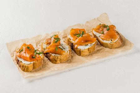 Брускетта с домашним лососем слабой соли, крем-чизом, листьями салата и вялеными томатами