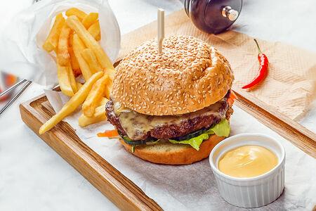 Гамбургер с сочной говяжьей котлетой, картофелем фри и сырным соусом