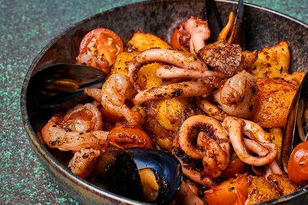 Креветки, кальмары и мидии, жаренные на планче с картофелем и томатами