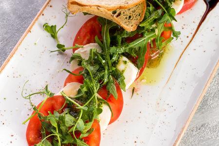 Моцарелла с томатами, рукколой и соусом Песто