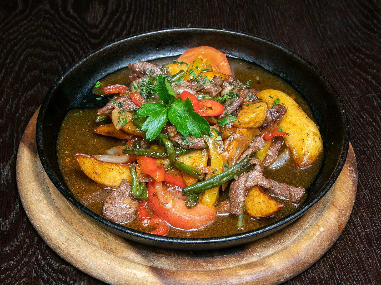 Горящая сковородка с говядиной и овощами