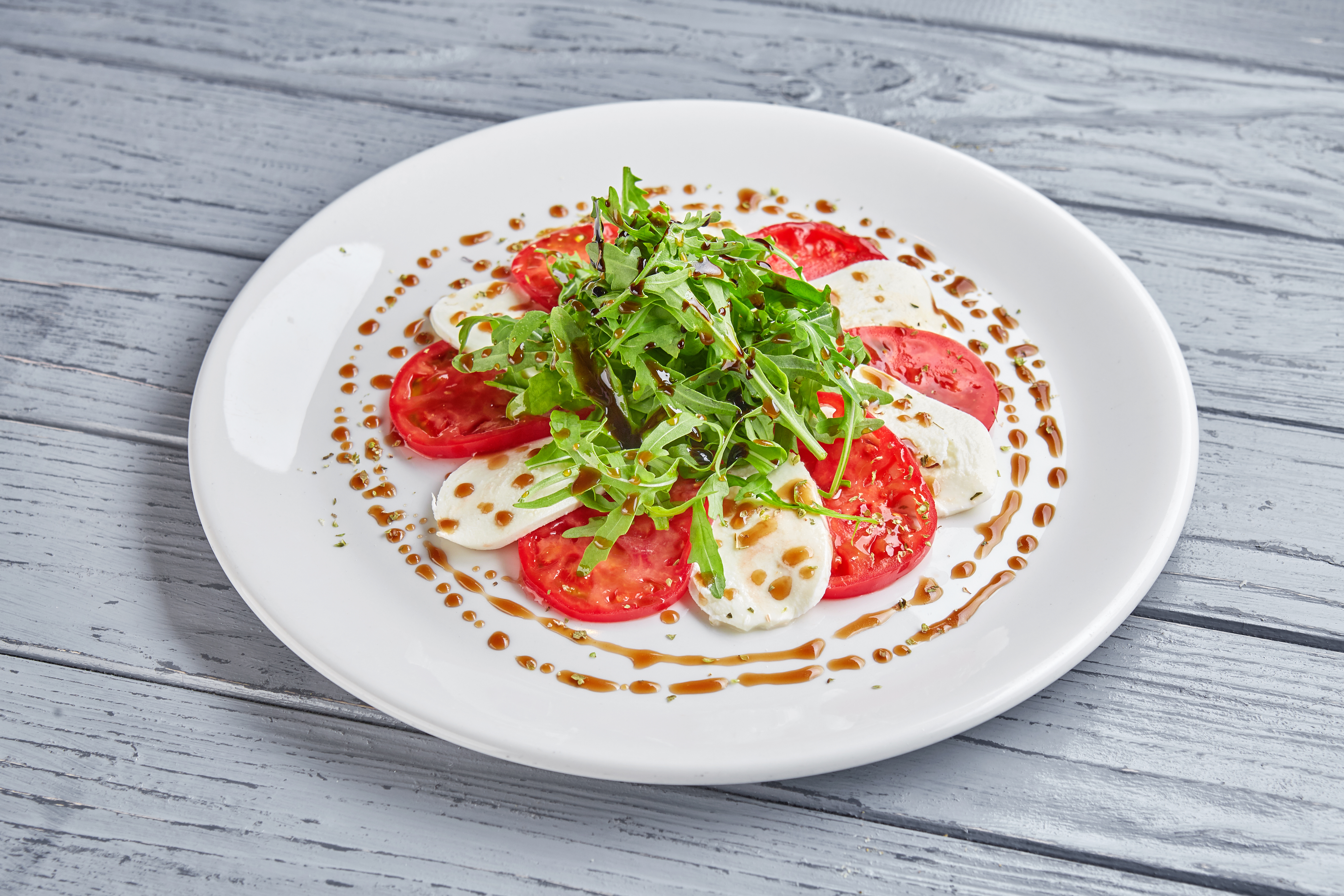 Капрезе сыр Моцарелла с томатами, хрустящей рукколой и соусом из медового бальзамика