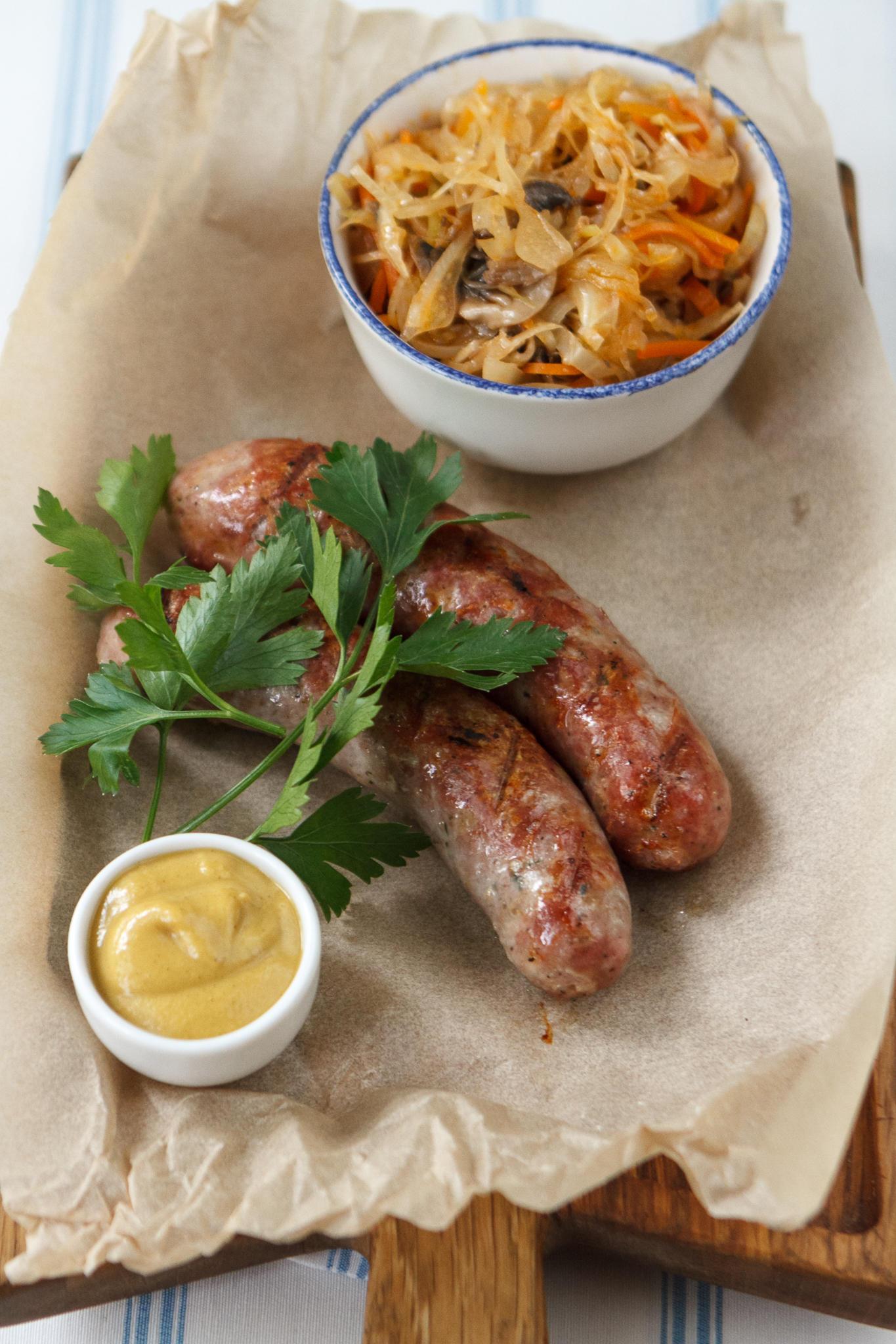 Свиные колбаски с тушеной капустой