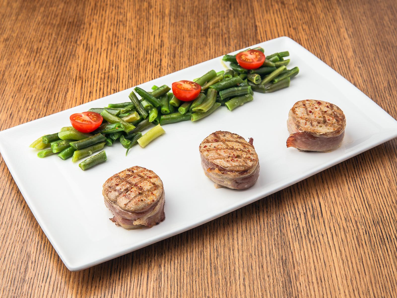Медальоны из свинины в беконе со стручковой фасолью и томатами черри