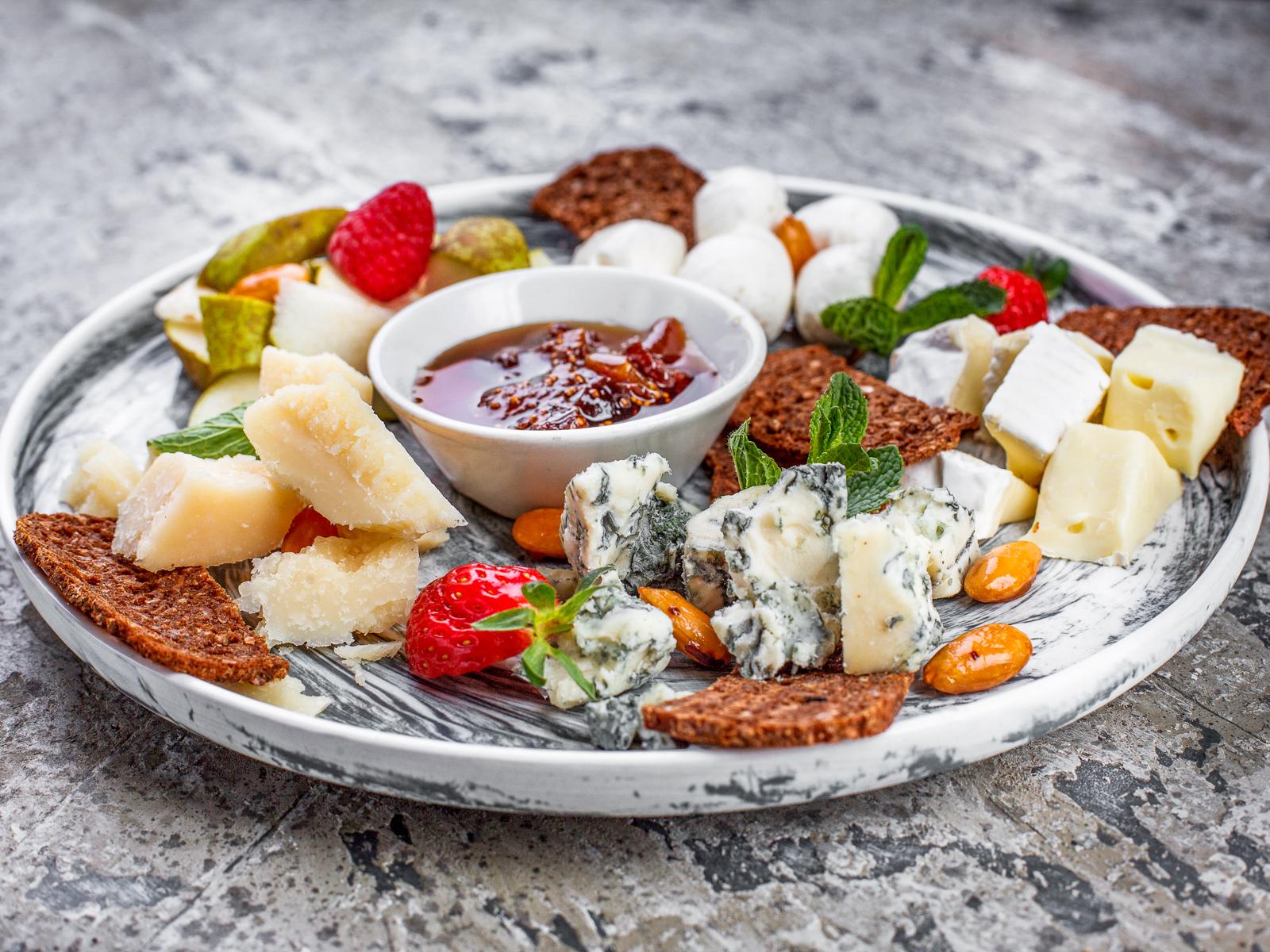 Сырная тарелка с сезонными фруктами и инжирным вареньем