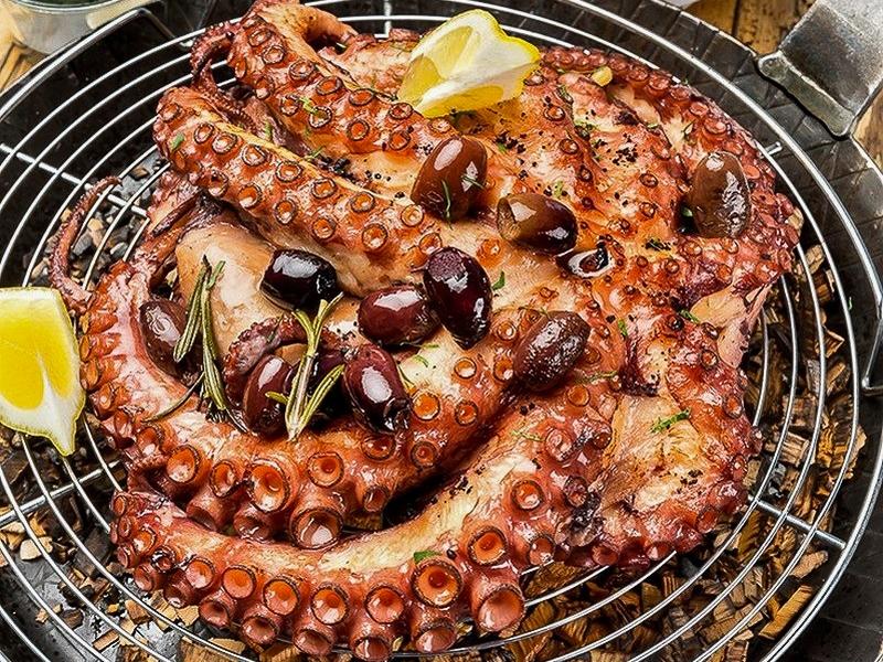 Целый осьминог с орзо и черным соусом айоли
