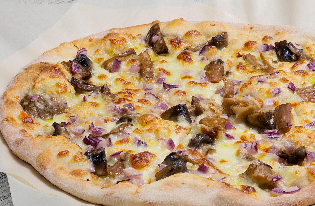 Пицца, в которой главную роль играют грибы: щедрые ломтики белых грибов соседствуют с шампиньонами